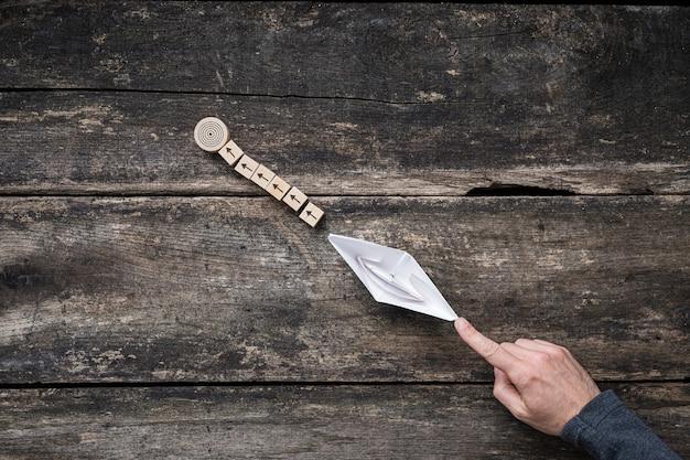 Geschäft, ausbildung oder persönliche ziele und ambitionen - männliche hand, die aus papier hergestelltes origami-boot drückt