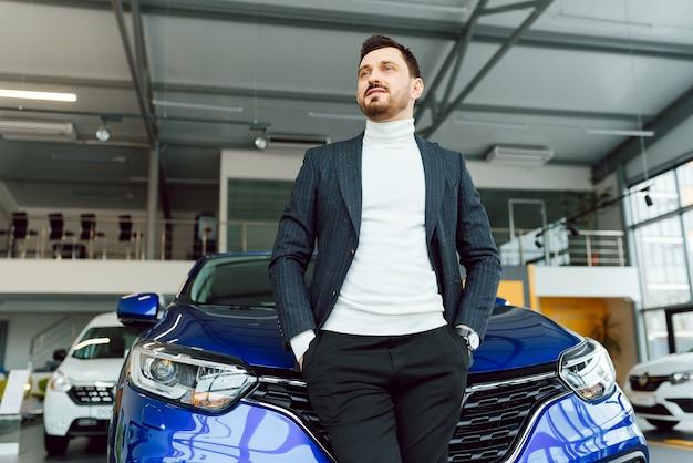 Geschäft, autoverkauf, konsumismus und personenkonzept - glücklicher mann über autoausstellung oder salonhintergrund