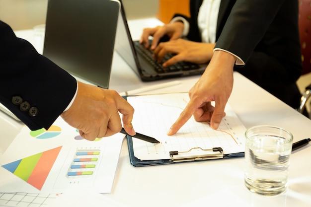 Geschäft, das finanzielle angelegenheitshände mit dem stift zeigt auf finanzdiagramm bespricht.
