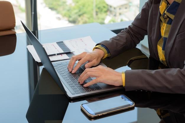 Geschäft, das im büro arbeitet: schließen sie herauf hand von den geschäftsfrauen, die laptop-computer auf einer tabelle schreiben.