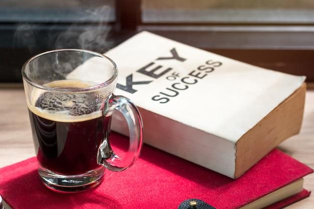 Geschäft des erfolgsbuches und des schwarzen kaffees auf hölzernem nahe fenster am hellen morgen