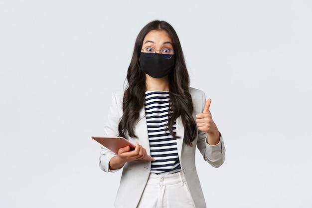 Geschäft, finanzen, covid-19-verhinderung von viren und konzept der sozialen distanzierung. beeindruckte asiatische büroleiterin von ihrer interessanten idee, daumen hoch, schutzmaske tragen und digitales tablet halten