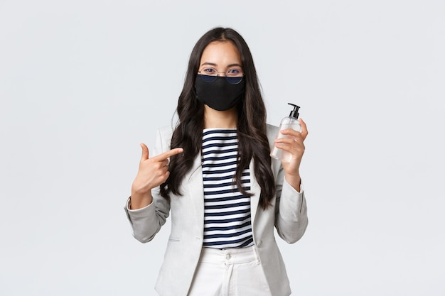 Geschäft, finanzen und beschäftigung, covid-19-verhinderung von viren und konzept der sozialen distanzierung. lächelnder süßer asiatischer büroangestellter in gesichtsmaske empfiehlt die verwendung von händedesinfektionsmittel während der arbeit