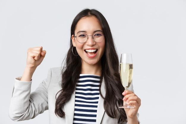Geschäft, finanzen und beschäftigung, konzept für erfolgreiche unternehmerinnen. fröhliche asiatische geschäftsfrau, die feiert, eine büroparty hat, champagner trinkt, vor freude singt, triumphiert