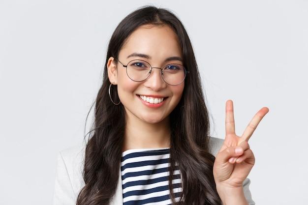 Geschäft, finanzen und beschäftigung, konzept für erfolgreiche unternehmerinnen. nahaufnahme eines freundlichen, ausgehenden asiatischen büroangestellten, der ein friedenszeichen zeigt und optimistisch lächelt, alles unter kontrolle haben