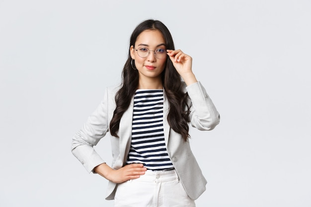 Geschäft, finanzen und beschäftigung, konzept für erfolgreiche unternehmerinnen. selbstbewusste geschäftsfrau in brille und weißem anzug bereit zum treffen, zufrieden lächelnd, entschlossen stehend