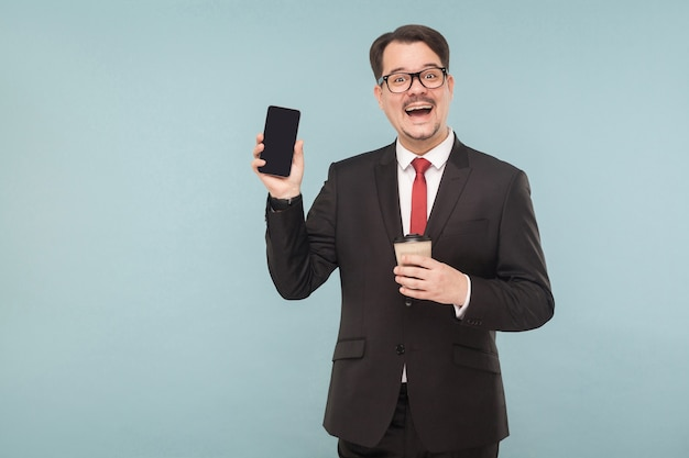 Geschäft, geräte, technologien. mann, der neues telefon zeigt. indoor, studioaufnahme, isoliert auf hellblauem oder grauem hintergrund