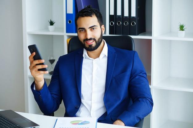 Geschäft. glücklicher geschäftsmann sitzt im hellen büro und hält