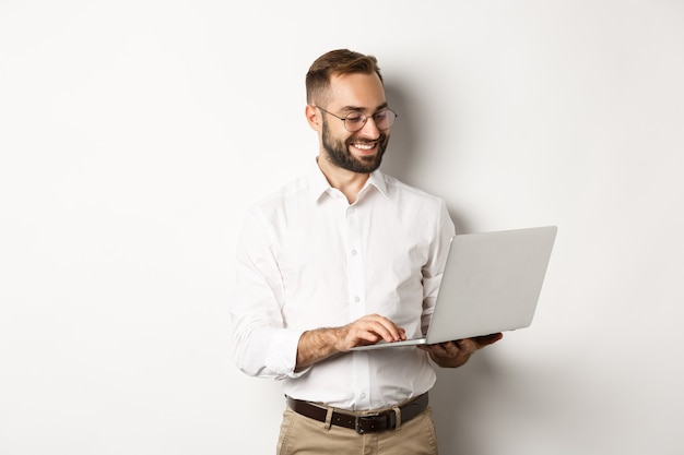 Geschäft. hübscher geschäftsmann, der am laptop arbeitet, nachrichten beantwortet und lächelt, stehend