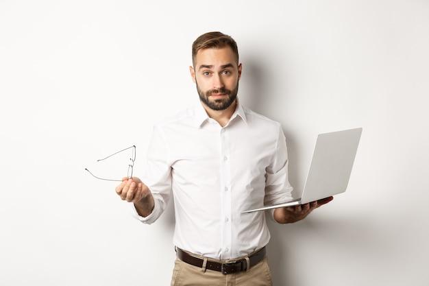 Geschäft. hübscher geschäftsmann, der verwirrt schaut, nachdem er mit laptop gearbeitet hat, stehend