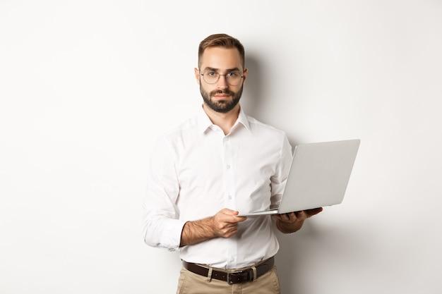Geschäft. hübscher manager, der am laptop arbeitet, computer hält und kamera betrachtet, stehend