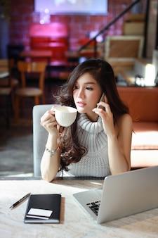 Geschäft in voller länge, das online, junge asiatische frau im freizeitkleid arbeitet an computer verkauft