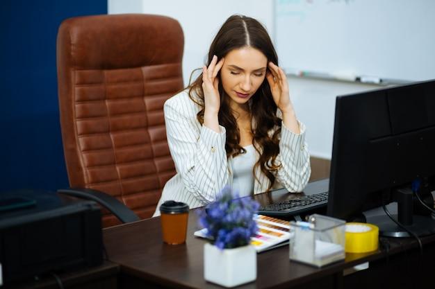 Geschäft konzipierte frau, die bei der arbeit sitzt und zwei hände hinter ihrem kopf hält