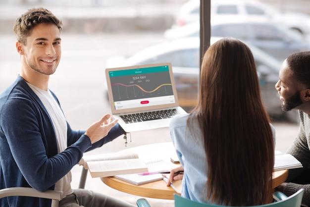 Geschäft lernen. glücklicher jugendlicher bärtiger mann, der laptop hält und informationen präsentiert, während er mit seinen gefährten in der modernen bibliothek sitzt.