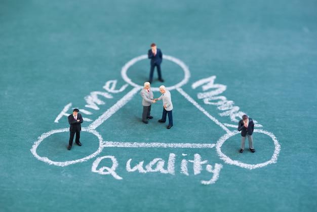 Geschäft miniaturmenschen, die hand in der balancenzeit, in der qualität und im gelddiagramm rütteln
