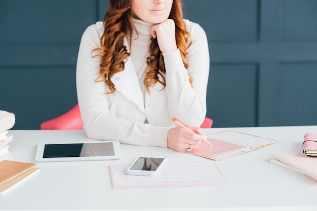 Geschäft mit sozialen netzwerken. internet marketing. smm-frau am arbeitsplatz notizen im zeitplan machen.