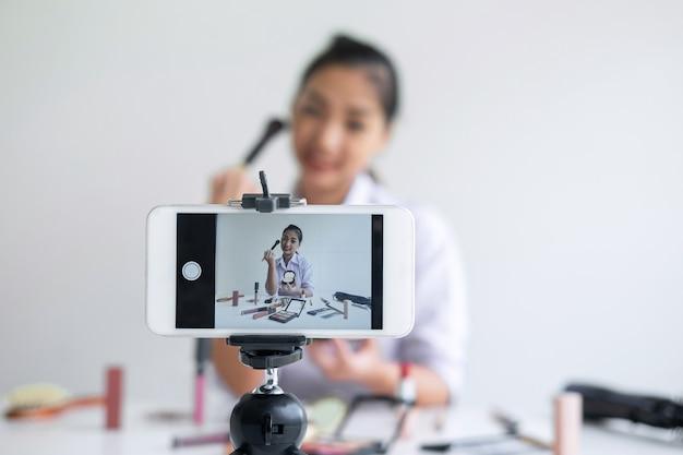 Geschäft online auf social media, schöner asiatinblogger zeigt anwesendes tutorialschönheitskosmetikprodukt und überträgt live-streaming-video zum sozialen netz, während er online unterrichtet