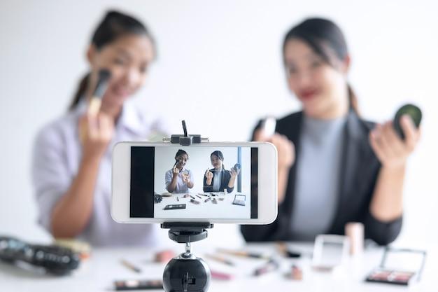 Geschäft online auf social media, zeigt der blogger mit zwei schönen frauen anwesendes kosmetisches produkt der tutorialschönheit und überträgt livestreamingvideo zum sozialen netz, während er online unterrichtet
