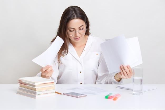 Geschäft schaut durch finanzdokumente, hat aufmerksamen blick, posiert auf dem desktop. professionelle anwältin prüft rechtliche informationen in papieren, gekleidet in stilvolle kleidung, brillen