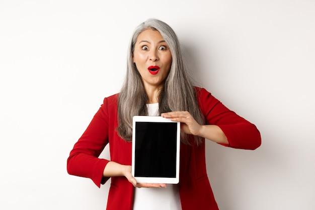 Geschäft. überraschte und glückliche asiatische unternehmerin, die werbung auf leerem digitalem tablettbildschirm zeigt und kamera erstaunt, weißen hintergrund anstarrt.