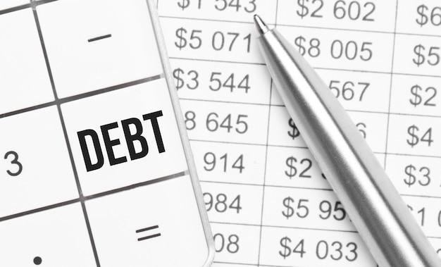 Geschäft und finanzen. auf dem tisch liegt ein bericht, ein stift und ein taschenrechner, auf dessen großem schlüssel debt . steht
