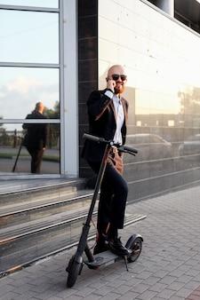 Geschäft und menschen und konzept. junger geschäftsmann, der elektroroller im freien reitet