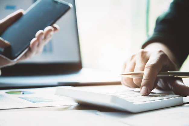 Geschäft und partnerschaft, die unter verwendung des taschenrechners sich besprechen, um die jahresbilanz mit behälter zu wiederholen und laptop-computer zur berechnung des budgets zu verwenden. prüfintegrität vor anlagekonzept.