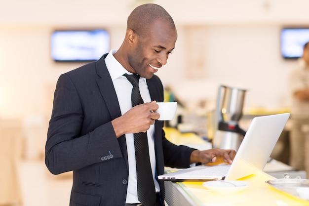 Geschäft unterwegs. fröhlicher junger afrikanischer mann in formeller kleidung, der seinen laptop benutzt, während er an der bar steht