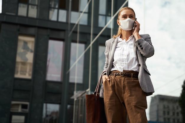 Geschäft während der koviden selbstbewussten geschäftsfrau, die eine schützende gesichtsmaske trägt und mit dem handy spricht