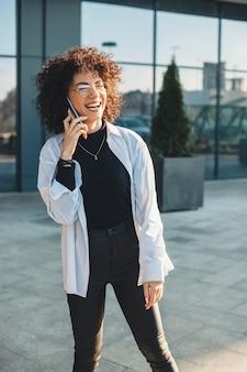 Geschäftige person des lockigen haares, die am telefon spricht, während sie lächelt und draußen eine brille trägt