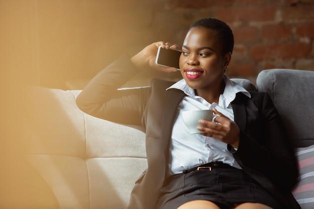 Geschäftlicher anruf. afroamerikanische geschäftsfrau in bürokleidung lächelnd, sieht selbstbewusst und glücklich aus, beschäftigt. konzept für finanzen, wirtschaft, gleichstellung und menschenrechte. schönes junges weibliches modell, erfolgreich.