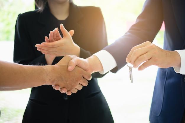 Geschäftliches partnerschaftstreffen und händeschütteln und geben schlüsselhaus. vereinbarung und immobilienkonzept.