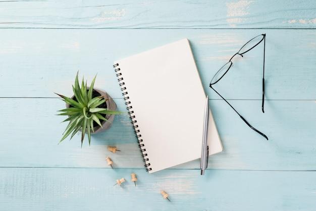 Geschäfts-, bildungs-, stillleben-, arbeits- oder planungskonzept: schreibtischtisch mit offenem notizbuchpapier, stift und brille, flacher lay, mock-up