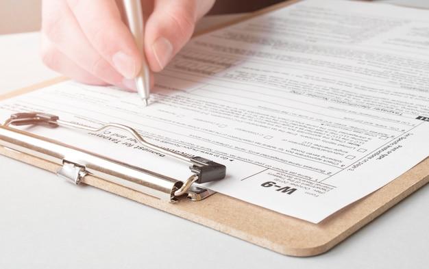 Geschäfts-, büro-, schul- und bildungskonzept - mann, der steuerformular ausfüllt