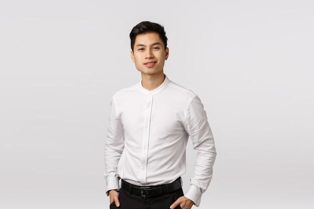Geschäfts-, erfolgs- und wohlfühlkonzept. der hübsche junge asiatische geschäftsmann, der mit finanzen arbeitet, haben glückliches dat, halten hände in den taschen und lächeln selbstsicher