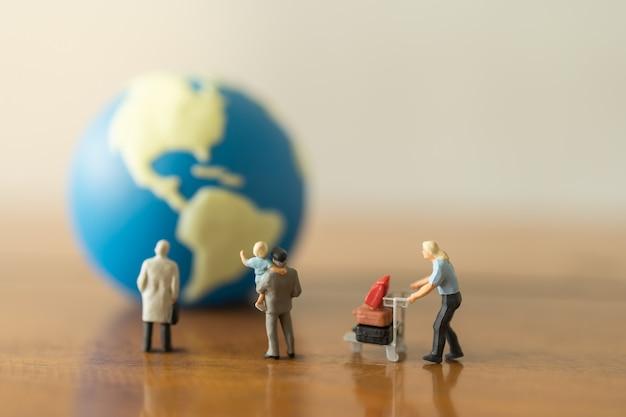 Geschäfts-, familienreisekonzept. gruppe von geschäftsmann, vater und kind und mann mit flughafengepäckwagen-miniaturfiguren, die zu mini-weltball auf holztisch und kopierraum suchen.