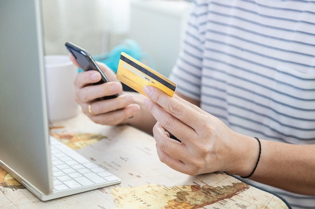 Geschäfts-, finanz- und e-commerce-konzept. nahaufnahme der mannhand, die gefälschte kreditkarte des modells mit mobilem smartphone mit computerdesktop hält.