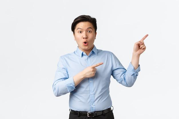 Geschäfts-, finanz- und menschenkonzept. überraschter und beeindruckter asiatischer männlicher unternehmer, büroleiter im blauen hemd, der auf die obere rechte ecke zeigt und erstaunt aussieht, sagen wow und starren die kamera in ehrfurcht an