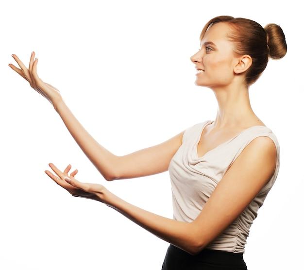Geschäfts-, finanz- und personenkonzept: junge geschäftsfrau zeigt finger. studioaufnahme getrennt auf weiß.