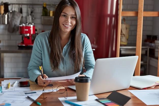 Geschäfts-, freiberufler- und arbeitskonzept. zufriedene weibliche ökonomin studiert dokumentation