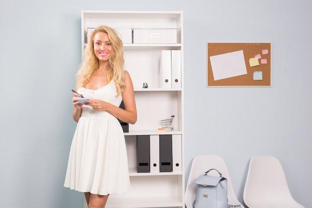 Geschäfts-, freiberufler- und personenkonzept - nahaufnahmeporträt der schönen frau im weißen kleid halten