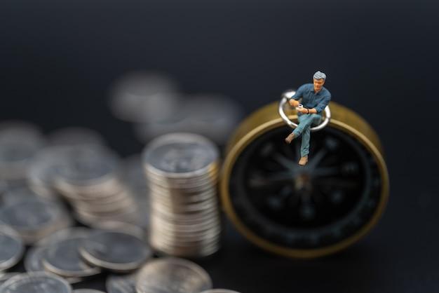 Geschäfts-, geld-, richtungs-, investitions- und planungskonzept. geschäftsmann miniaturfigur menschenfigur sitzt auf vintage kompass mit tasse kaffee und stapel silbermünzen auf schwarzem hintergrund.