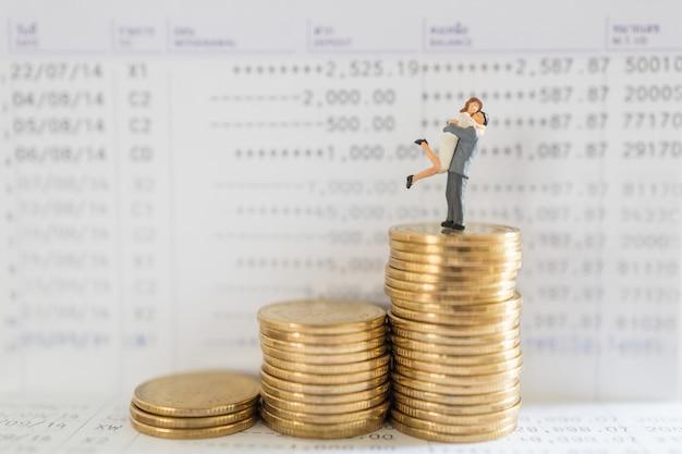 Geschäfts-, geld-, spar-, sicherheits- und paarfamilienkonzept. nahaufnahme von mann und frau miniaturfigur menschen umarmen und stehen auf stapel goldmünzen auf bank sparbuch mit kopie raum.