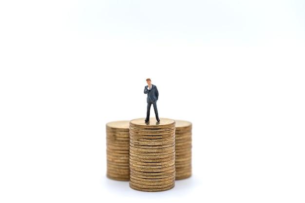 Geschäfts-, geldanlage- und planungskonzept. geschäftsmann miniaturfigur menschenfigur stehend auf stapel von goldmünzen auf weißem hintergrund.