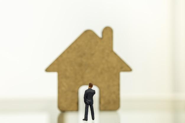 Geschäfts-, hypotheken- und wohnungsbaudarlehenskonzept. schließen sie oben von geschäftsmann-miniaturfigurmenschen, die stehen und zu hölzernem hausikonen-symbol mit kopienraum suchen.