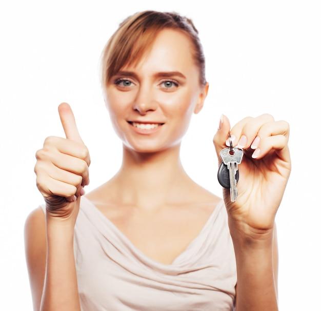 Geschäfts-, immobilien- und bürokonzept: junge geschäftsfrau mit schlüssel. positive emotionen. getrennt auf weiß.