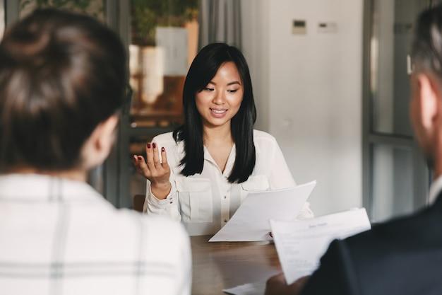 Geschäfts-, karriere- und vermittlungskonzept - geschäftsmäßige asiatische frau, die einen lebenslauf hält und mit arbeitgebern eines großen unternehmens während eines unternehmenstreffens oder eines vorstellungsgesprächs spricht