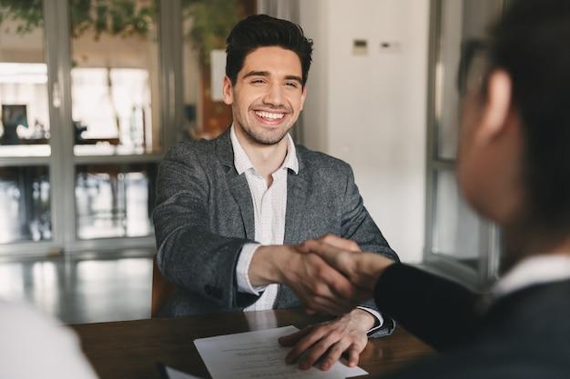 Geschäfts-, karriere- und vermittlungskonzept - glücklicher 30-jähriger kaukasischer mann, der sich freut und dem mitarbeiter die hand schüttelt, als er während eines interviews im amt eingestellt wurde