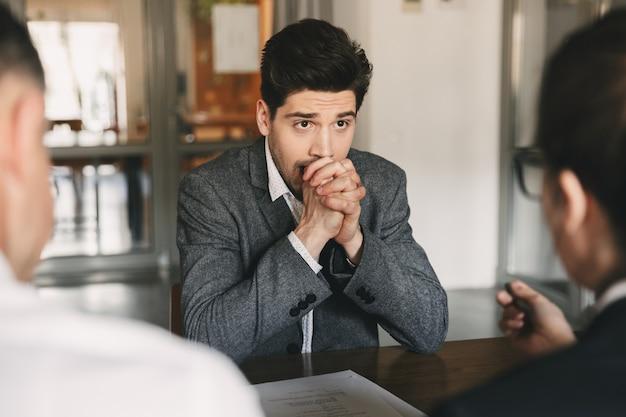 Geschäfts-, karriere- und vermittlungskonzept - kaukasischer, angespannter männlicher bewerber, der sich während des vorstellungsgesprächs im amt mit dem verwaltungsrat sorgen macht und fäuste zusammensetzt