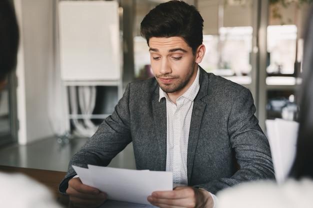 Geschäfts-, karriere- und vermittlungskonzept - kaukasischer mann der 30er jahre, der seinen lebenslauf oder seine dokumente während eines vorstellungsgesprächs im amt mit einem ausschuss geschäftsmäßiger personen liest